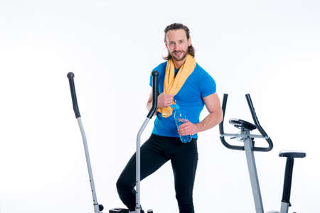 fitnesscenter: young man train with fitness machine and drinking water
