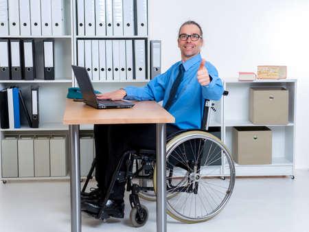 paraplegic: hombre de negocios de personas discapacitadas en silla de ruedas con el pulgar arriba