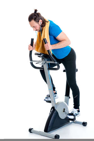 fitnesscenter: young man train with fitness machine in front of white background