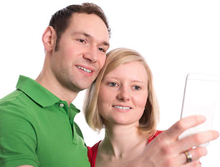 self   portrait: young couple in an embrace in front of white background taking a self portrait Stock Photo
