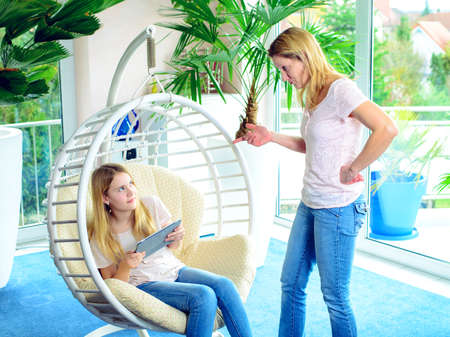 bluster: girl using too much her tablet computer and her mother is angry Stock Photo
