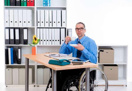 paraplegic: disabled business man in wheelchair is drinking coffee Foto de archivo