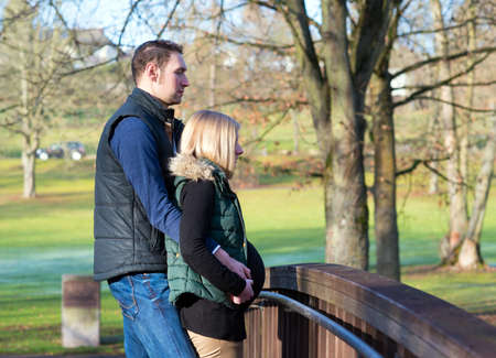 endearment: young man and his pregnant wife in the park Stock Photo