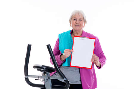 sports programme: gray-haired female senior with clipboard train with fitness machine Stock Photo