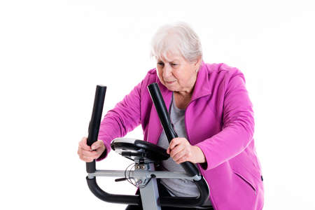 gray-haired female senior train with fitness machine Stock Photo