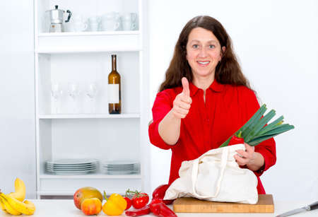 dark haired woman: dark haired woman with thumb up in the kitchen