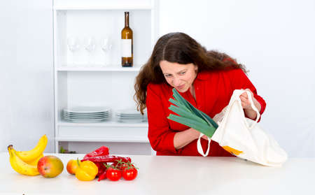 dark haired woman: dark haired woman with red shirt in the kitchen