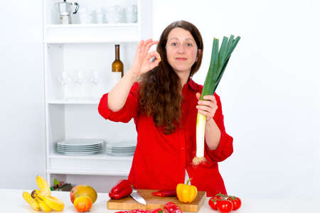 dark haired woman: dark haired woman the kitchen showing delicious gesture Stock Photo