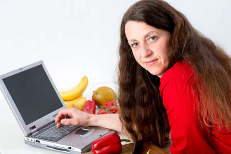 dark haired woman: dark haired woman in the kitchen using computer