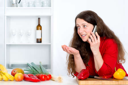 red shirt: dark haired woman with red shirt in the kitchen is calling