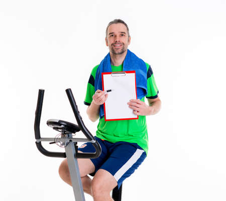 fitnesscenter: young man with clipboard train on fitness machine
