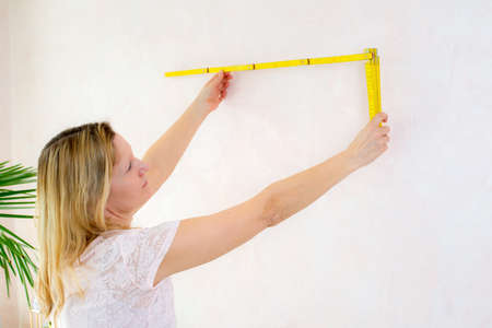 redecorate: blond woman redecorate home and working with folding yardstick Stock Photo