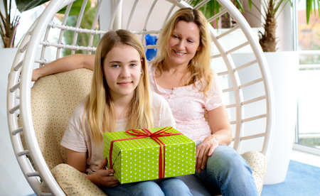 blonde teenager: mother and daughterl with green gift box in a chair