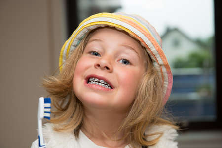 little funny girl with retainer and toothbrush looking in to the camera