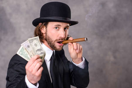 bowler: young businessman with bowler hat and big cigar and money Stock Photo