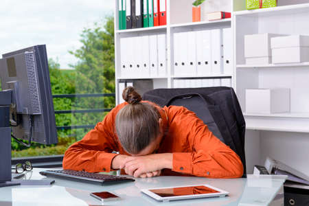 overwrought: young tired business man lying with head on his desk