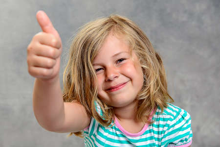 jubilating: funny girl with thumb up in front of gray background