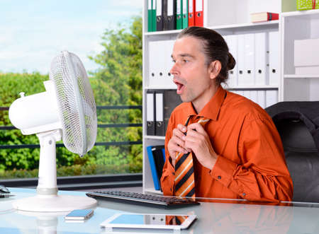 perspiration: young business man with ventilator at his desk in summerly hot office