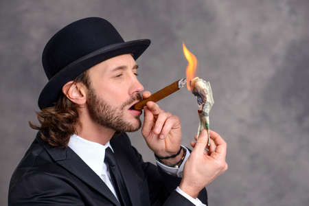 bowler: young businessman with bowler hat lighting big cigar with money Stock Photo