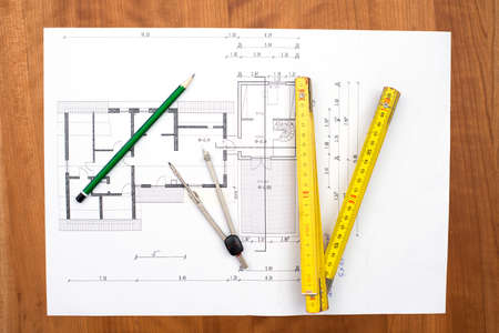 yardstick: building plan with pencil, folding yardstick and compass on wooden table Stock Photo