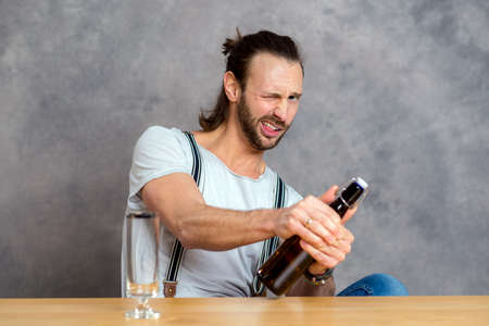 skoal: young man in front of gray background opening a beer bottle