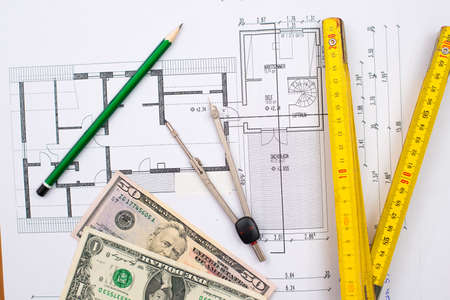 building plan with money pencil folding yardstick and compass