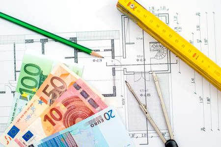 bouwplan met geld potlood opvouwbare meetlat en kompas