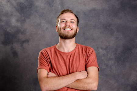 red shirt: portrait of a young friendly, bearded man in red shirt