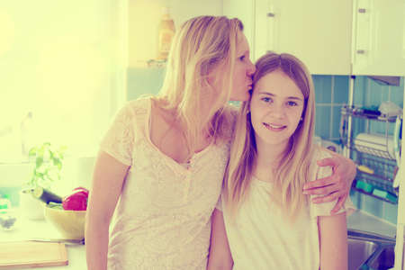 hugged: blond mother hugged her daughter at home
