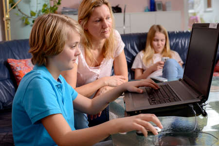 blond mother and her children using computer together
