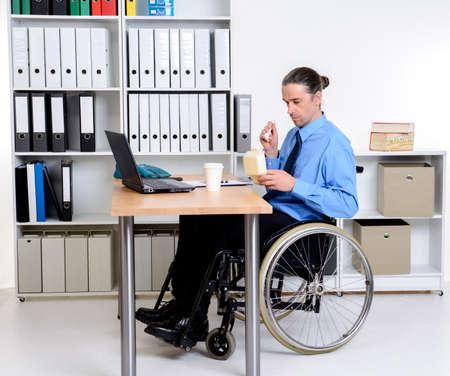 paraplegico: hombre de negocios de personas discapacitadas en silla de ruedas de comer en la oficina Foto de archivo