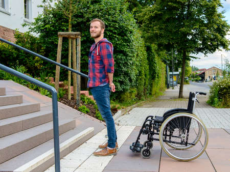 paraplegic: young man standing with wheelchair in front of stairs