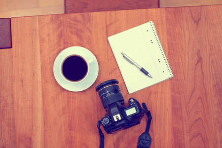 scratchpad: camera, notepad with pen and coffee on wooden table from above