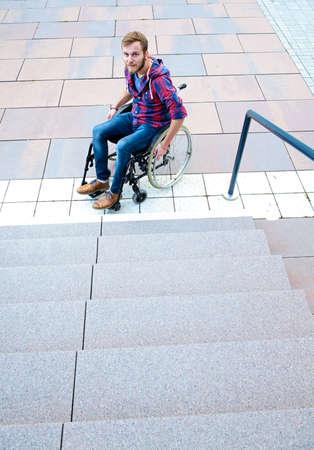 joven discapacitado en silla de ruedas bajo escalera