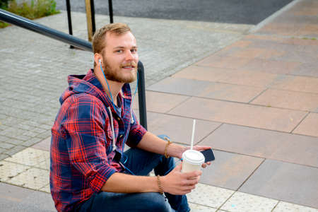 musik: young man with soft drink sitting on stairs and using his smartphone Stock Photo