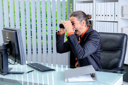exultation: young amazed business man looking with binoculars at the screen Stock Photo