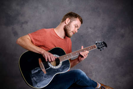 red shirt: young bearded man in red shirt playing acoustic guitar