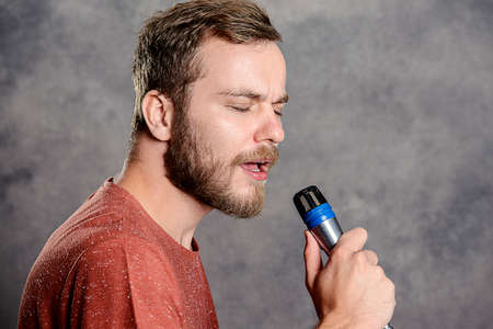 red shirt: young bearded man in red shirt singing in microphone