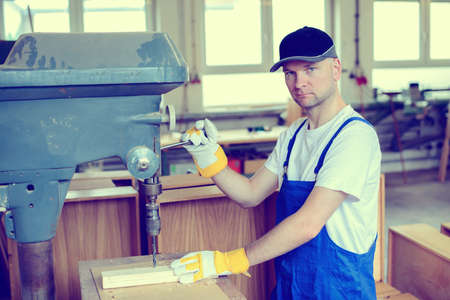 bib overall: worker with dark cap in a carpenters workshop using drilling machine