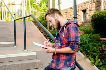 writ: young man bearded standing by stairs with clipboard and writing