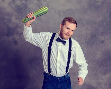 a cudgel: young angry vegetarian minatory with zucchini cudgel