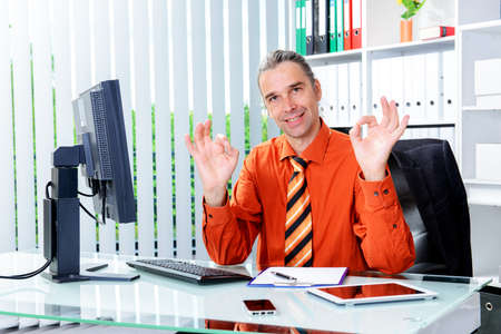 alright: young business man at his desk showing alright Stock Photo