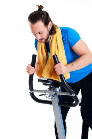 fitnesscenter: young man in blue shirt train with fitness machine and listening music