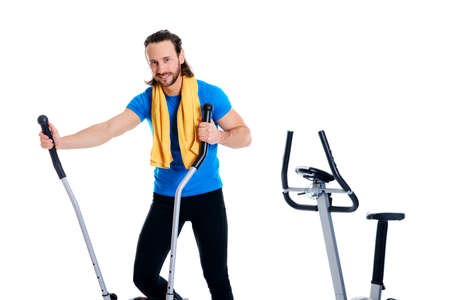 young man in blue shirt train with fitness machine and listening music