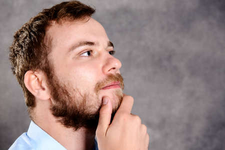reflecting: young bearded man in front of gray background is reflecting