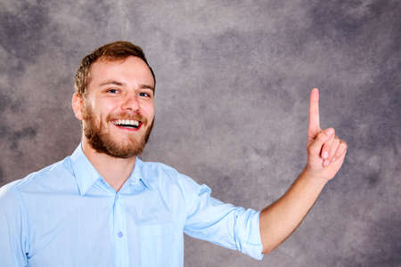 forefinger: young bearded man is surprised and showing forefinger Stock Photo