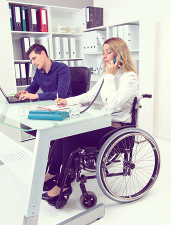 paraplegic: disabled businesswoman in wheelchair and her colleague in the office Stock Photo