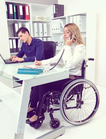 paraplegico: empresaria personas discapacitadas en silla de ruedas y su colega en la oficina