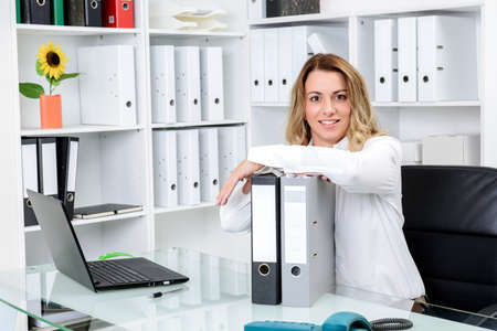 company job: young blond businesswoman working in the office