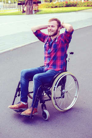young disabled man in wheelchair on road is smiling